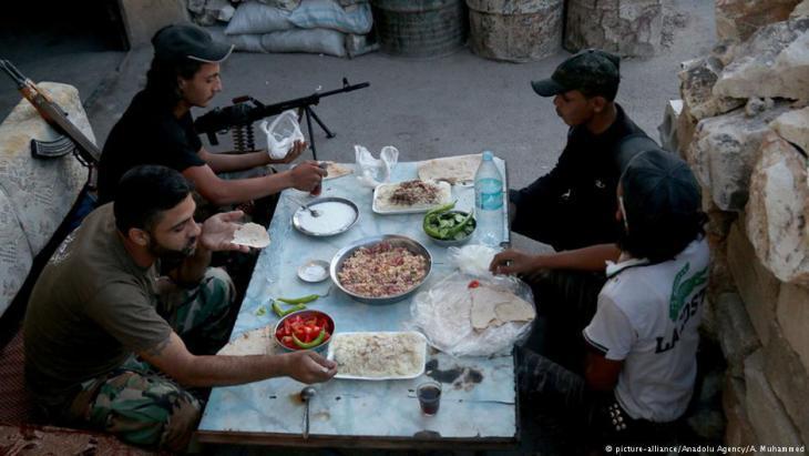 مقاتلون تابعون للمعارضة السورية أثناء تناول وجبة الإفطار في رمضان.
