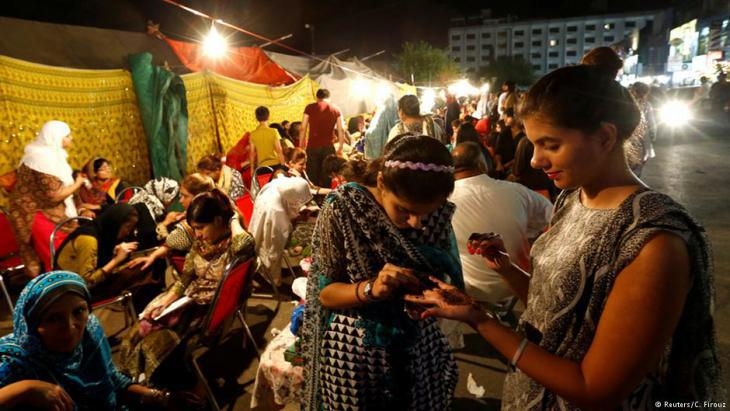 فتيات في باكستان ينقشن أيديهن بالحناء استعداداً لعيد الفطر.