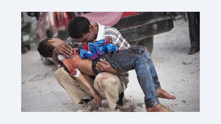 والد يحمل ابنه القتيل برصاص قوات الجيش السوري. أ ب