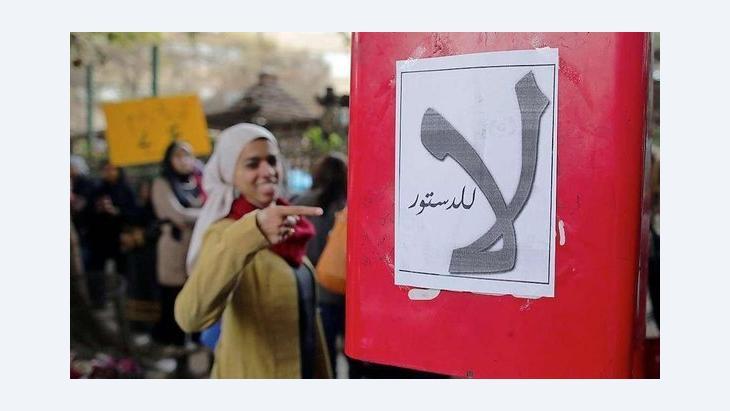 ناشطة تشير إلى لوحة مكتوب عليها: ''لا للدستور''. د ب أ