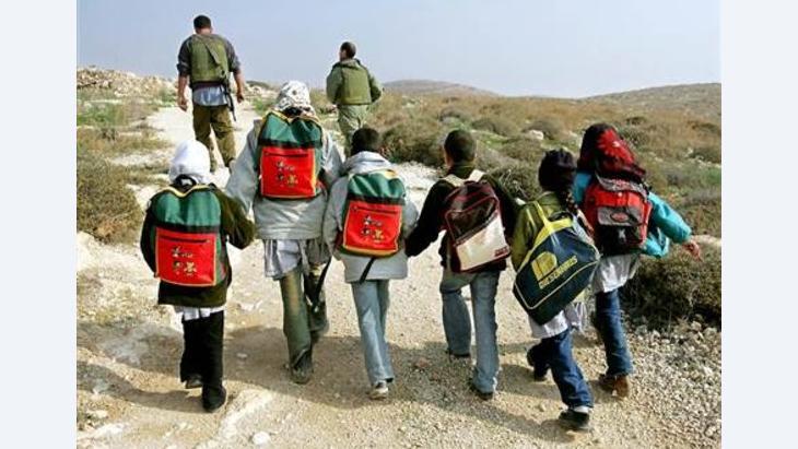جنود  إسرائيليون يقومون بحماية طلبة فلسطينيين من هجمات المستوطنين