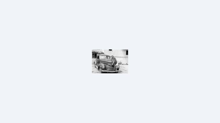 رجل يجلس على غطاء محرك سيارته، الصورة: المؤسسة العربية للصورة