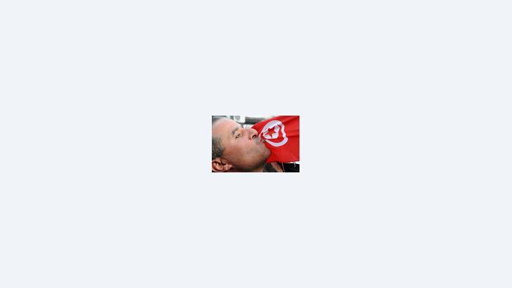 متظاهر تونسي يقبل علم بلاده، الصورة ا.ب