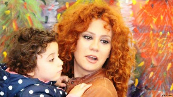الفنانة لينا شامَميان تحتضن طفلا سوريا لاجئا