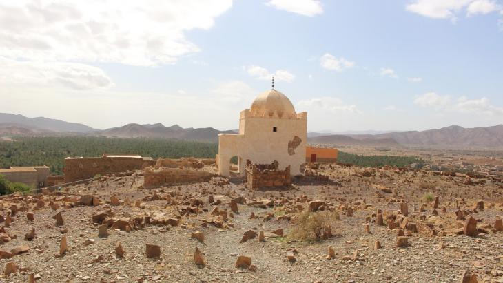 """قمة قرية """"أكادير لِهنا"""" يعلوها ضريح لأحد المتصوفة، من حوله تنتشر قبور أهل القرية ويلاحظ عدم التكلّف في بناء القبور بل فقط استخدام الأحجار كعلامات."""