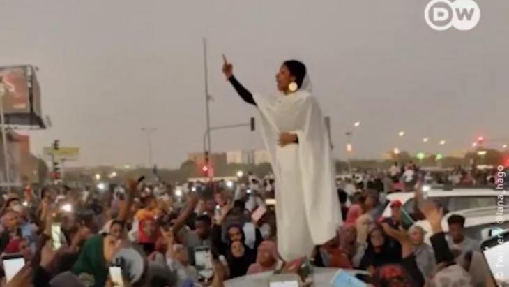 """""""حبوبتي كنداكة"""".. امرأة سودانية تتحول لأيقونة """"الثورة"""". إعتلت امرأة سودانية سقف سيارة في الخرطوم وألقت من """"منبرها"""" شعرا وغناء وسط حشود متحمسة رددت بعد كل مقطع """"ثورة"""". وتحولت المرأة التي تدعى آلاء صلاح إلى أيقونة الاحتجاجات في البلاد، وتقاسم العديد عبر العالم الفيديو الذي يظهرها وهي تطلق الهتافات التي يرددها المتظاهرون وراءها."""