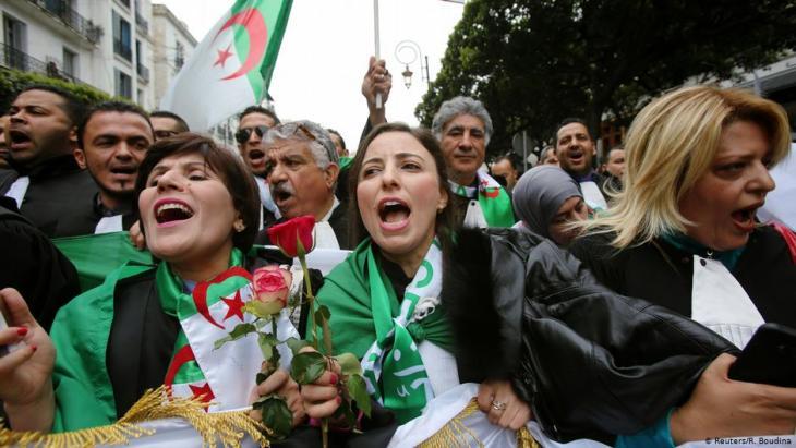 """رغم سوء الأحوال الجوية، خرج آلاف الجزائريين إلى الشوارع، مرددين شعارات تنتقد تنظيم انتخابات مبكرة، ودعوا إلى """"تحرير العدالة والإعلام"""" و""""إعادة السلطة للشعب"""". وجاءت المظاهرات في وقت تحتفل فيه الجزائر بالذكرى 59 لعيد النصر."""