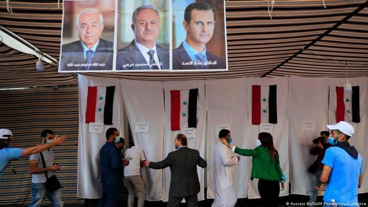 لجنة اقتراع لمواطنين سوريين في لبنان في خيمة. مقصورات الاقتراع معزولة بستارات معلقة عليها الأعلام السورية. تتدلى صور المرشحين الثلاثة من السقف.