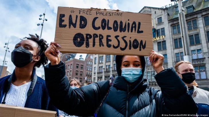 """أمستردام - هولندا - مايو / أيار 2021: امرأة تحمل لافتة  ضد الاستعمار خلال مظاهرة. آلاف الهولنديين في """"ساحة دام"""" في أمستردام ينددون بالعمليات الإسرائيلية وخطط الإجلاء القسري للفلسطينيين من حي الشيخ جراح بالقدس الشرقية المحتلة."""