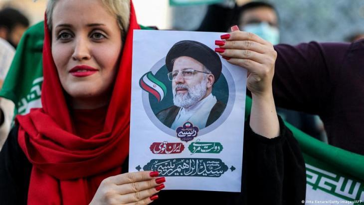سيدة إيرانية تحمل صورة الرئيس الإيراني الجديد إبراهيم رئيسي بعد فوزه المتوقع بالانتخابات.
