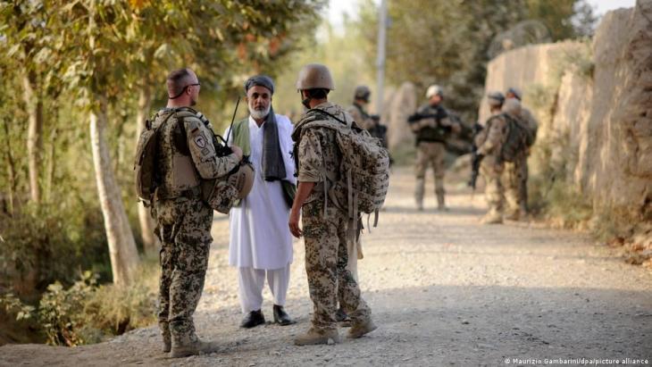 جندي من الجيش الألماني (يسار) ومترجم فوري (يمين) يتحدثان إلى رجل بالقرب من مدينة قندوز في منطقة شار دارا.