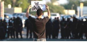 متظاهر في البحرين يحمل صورة المُعتقَل حسن المشيمع. نوفمبر 2012. أ ب