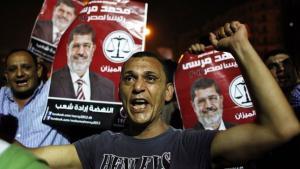 أنصار لجماعة ''الإخوان المسلمون'' يرفعون صورة الرئيس مرسي عالياً في إحدى المظاهرات. أ ب