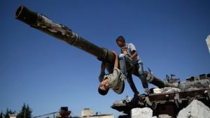 أطفال يلعبون على دبابة في حلب. أ ب