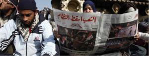 سيدة مصرية تتصفح جريدة الاهرام بهد سقوط مبارك