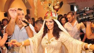 """حفلة """"حنة"""" ليهود من أصول عراقية في إسرائيل على أنغام موسيقى شرقية وعراقية قدمها المطرب راني كوهين وأحيتها الراقصة غال وهي تضع شمعدانا على رأسها."""