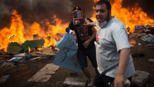 أنصار مرسي يهربون من تصاعد اللهب ضدهم في القاهرة، لهب في الخلفية. dpa/AP