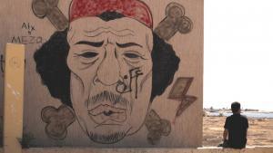 رجل جالس إلى جانب جدارية عليها صورة القذافي في مدينة بنغازي الليبية. photo: AP