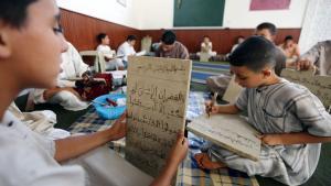 أطفال ليبيون يكتبون على ألواح خشبية في إحدى مدارس تحفيظ القرآن خلال شهر رمضان بهدف تعلم الآيات القرآنية عن ظهر قلب بتاريخ 20 / 07 / 2012 في العاصمة الليبية طرابلس. photo: Mahmud Turkia/AFP/Getty Images