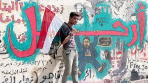 شاب مصري بجانب رسم جداري مناوئ لمرسي في القاهرة. Foto: picture-alliance/dpa