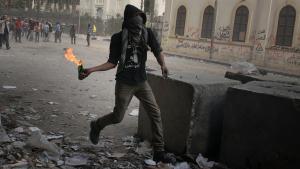متظاهر، محتج على الحكومة المصرية الجديدة بقيادة الجيش، يرمي عبوات حارقة على عناصر الأمن في القاهرة. Foto: dpa/picture-alliance