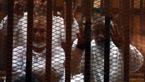 مرشد الإخوان المسلمين محمد بديع (إلى اليمين) وعضو آخر في جماعته في قفص الاحتجاز والمحاكمة في القاهرة.  Foto: dpa/picture-alliance