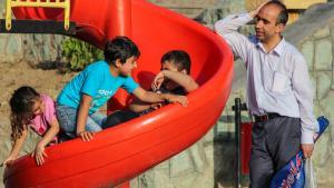 أب إيراني مع أبنائه الثلاثة في حديقة لعب الأطفال.  Foto: ISNA