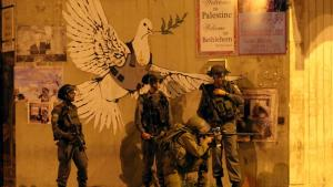 """مجموعة من الجنود  يطلقون  النار  على شبان  يحتجون على الحرب في غزة  من تحت شعار """"حمامة السلام""""  رسمة على مدخل مدينة بيت لحم -تصوير مهند حامد"""