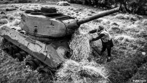 حصاد عند أنقاض دبابة: تركت الـ30 سنة، التي تلت الغزو السوفييتي لأفغانستان مرورًا بحكم طالبان وحتى مهمة قوَّات الإيساف، آثارها في جميع أنحاء البلاد. آثار يواجهها الناس في حياتهم اليومية ويعيشون معها. يقوم هذا الفلاح، على سبيل المثال، بتحميل محصوله فوق هيكل دبابة تعود إلى حقبة الاحتلال السوفييتي الممتدة من عام 1979 وحتى عام 1989.
