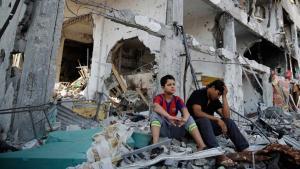 شابان جالسان هلى حطام منزلهما في غزة. Foto: Reuters
