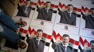 رجل يدهس بقدميه لوحة دعائية انتخابية للرئيس السوري بشار الأسد. Foto: Phil Moore/AFP/Getty Images