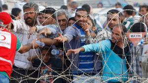لاجئون سوريون على الحدود يحصلون على ماء من الهلال الأحمر التركي. photo: Reuters/Murad Sez)