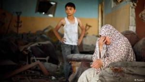 عائلة فلسطينية في دمار منزلها. Foto: Reuters