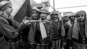 """الممثلون -الذين يعيدون تجسيد معركة كربلاء- مجتمعون خلف  مسرح العرض. ويلعب هؤلاء الرجال (على الصورة) أدوار الأمويين السنة الذين حاربوا جيش الحسين، وقاموا في نهاية المطاف بقتله. ومن خلال تجسيد عملية الإعدام يلمّح الممثلون بتهكم إلى مقاتلي تنظيم """"الدولة الإسلامية"""" السنة (داعش)، الذين أدخلوا اليوم الرعب إلى المنطقة عبر قطع رؤوس الرهائن والمقاتلين الخصوم."""