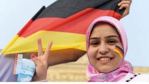 صورة لمسلمة مع العلم الألماني. Foto: dpa/pictue-alliance