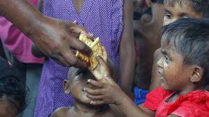 طفل لاجئ ينتمي للروهينغا المسلمين يتناول قطعة بسكويت من أحد المتطوعين في إندونيسيا. (photo: Reuters/Beawiharta)
