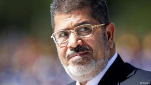محمد مرسي الرئيس المصري الأسبق، الذي قام الجيش المصري بعزله في أعقاب تظاهرات شعبية انطلقت في الثلاثين من يونيو/ حزيران. كان مرسي أول رئيس منتخب بعد ثورة 25 يناير وقبلها الناطق باسم الكتلة البرلمانية لنواب الإخوان بين عامي 2000 و2005.