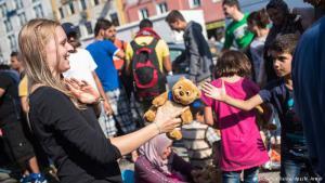 بالود والترحاب تستقبل هذه الشابة من جماعات المتطوعين صغار اللاجئين، الذين يتبادلون معها التحية. يقوم المتطوعون بفرز المساعدات وترتيبها وتوزيعها على اللاجئين. ورغم العمل الشاق لا ينسون الابتسامة ليدخلوا الطمأنينة إلى قلوب اللاجئين الذين روعتهم مناظر القتل والعنف في بلادهم الأصلية وواجهتهم الأهوال في طريق رحلتهم.