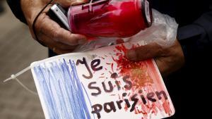 """متضامن مع ضحايا هجمات باريس يحمل لوحة مكتوب عليها: """"أنا باريسي"""". Foto: Reuters/K. Pempel"""