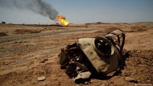 مركبة عسكرية محطمة عند بئر نفطية محترقة. (photo: picture-alliance/dpa)