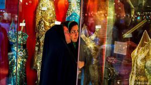شابتان بالشادور التقليدي تتأملان ملابس عصرية للسهرة عبر زجاج إحدى محلات بيع الملابس في طهران. ارتداء ملابس مثل المعروضة في الواجهة الزجاجية ممنوع بشكل مطلق في إيران.