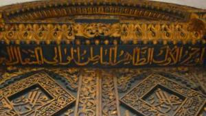 """بوابة في قصر """"بيت العجائب"""": رمز للمكانة والثراء - توجد في جميع أنحاء المدينة القديمة في ستون تاون أبواب وبوَّابات كبيرة على مداخل المباني زيِّنت بأشكال هندسية وزخارف كما أنَّها تدل على أصول أصحاب هذه المباني. وتشير الزخارف والنقوش وأعمال تطعيم الخشب الموجودة على هذه الأبواب والبوَّبات إلى تنوّع التقاليد العربية والهندية والسواحلية.  في الصورة: بوَّابة زيِّنت بآيات قرآنية في """"بيت العجائب""""."""