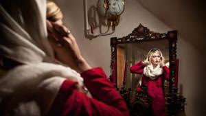منديل على الشعر الأشقر ومعطف فوق الملابس الغربية: امرأة إيرانية تستعد لمغادرة منزلها. الجمال المثالي في إيران يفرض التوازن بين التقاليد والحداثة، مثلما تبيِّن المصوِّرة سمانه خسروي. الكثير من الإيرانيات يرغبن الظهور مثل ممثِّلات هوليوود، اللواتي يتابعنهن من خلال الإنترنت أو القنوات الفضائية.