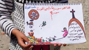 """عبرت طفلة سورية عمرها نحو 10 سنوات، خلال تواجدها في مخيم للاجئين في اليونان، عن قصص الخوف والحزن التي عاشتها. بالرسم وبكلمات بسيطة عكست الأوضاع المأساوية للسوريين. رسمت قبرا لوالديها ولسوريين آخرين، ودبابات وطائرات تدك منازل سطعت فوقها """"شمس الموت""""، بحسب تعبيرها."""