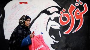 امرأة تمشي قرب جدارية في القاهرة. Foto: Getty Images/AFP/F. Monteforte