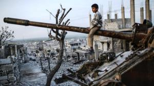 طفل سوري يلعب على دبابة مدمَّرة. Getty Images