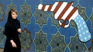 امرأة إيرانية تمشي بجوارحائط مرسوم عليه مسدس عليه ألوان العلَم الأمريكي .