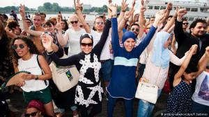 """إنه ليس شاطئا حقيقيا، والمكان ليس في فرنساـ ورغم ذلك تحرك نحو مائة من النساء والرجال البلجيكيين ضد ـ حظر لباس البوركيني الذي علقته محكمة فرنسية. وقالت امرأة خلال تلك التظاهرة:""""كل امرأة وكل رجل له الحق في اختيار لباسه""""."""