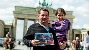 لاجئ عراقي مع ابنته عند بوابة براندنبورغ في برلين. Foto: picture-alliance/dpa/J. Carstensen