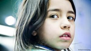 """إلهام طفلة كردية سورية في التاسعة من عمرها. لاحظ المصور دانييل ما تخفيه عيناها من حزن عميق، إلا أنها قد تبدو سعيدة في أوقات أخرى كباقي الأطفال من عمرها، حين تلعب بمرح وتضحك. أشار دانييل إلى أن ما يميز هذه الطفلة هو أنها """"عندما تكون سعيدة هناك مزيج من السعادة والحزن يظهر في ملامحها بشكل مميز وغريب جداً""""."""